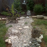 Photo Thumbnail #1: old wheelbarrow and tree stump with frog...