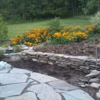 Photo Thumbnail #22: Building a stone retaining wall in our back yard.